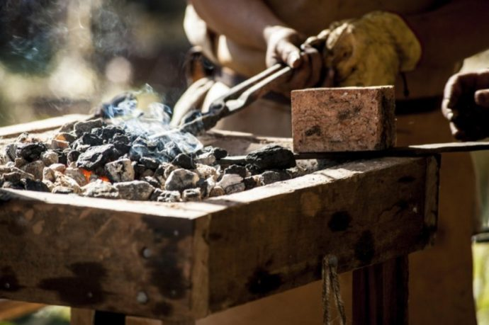 Closeup of medieval blacksmith's brazier showing blacksmith's hands holding traditional blacksmith's iron tongs grasping a piece of metal being heated in the coals before being hammered into a sword.