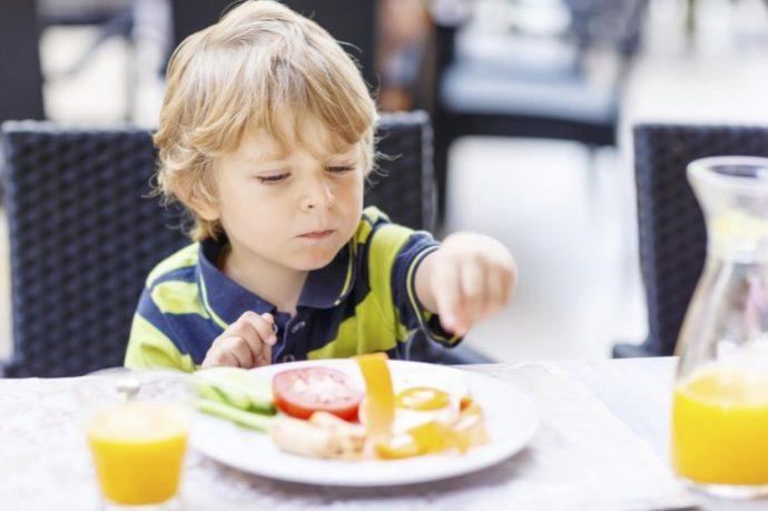 Little kid boy having healthy breakfast in hotel restaurant or city cafe.