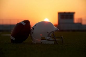 American Football and Helmet on the Field Backlit at Sunset with Sun glare for effect