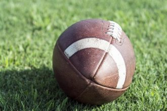Close up of American football sitting on real green grass
