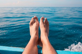 Male relaxing his feet over the edge of boat. Travel concept.